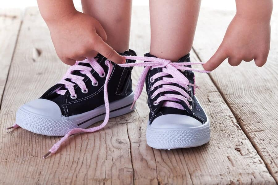 child tying her shoes