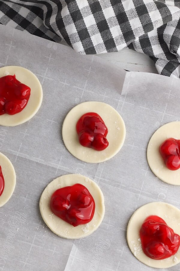 pie dough circles with cherry pie filling on top