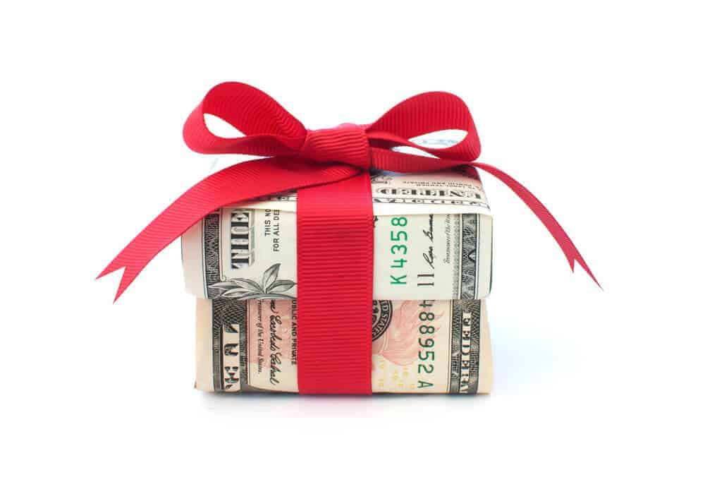 gift box made out of money with red bow