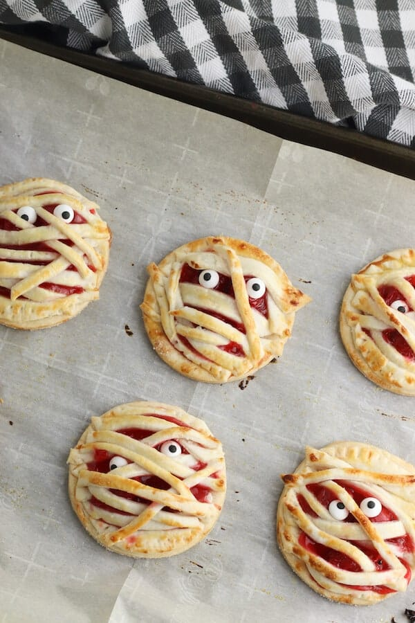 mini mummy cherry pie Halloween treats on a baking sheet