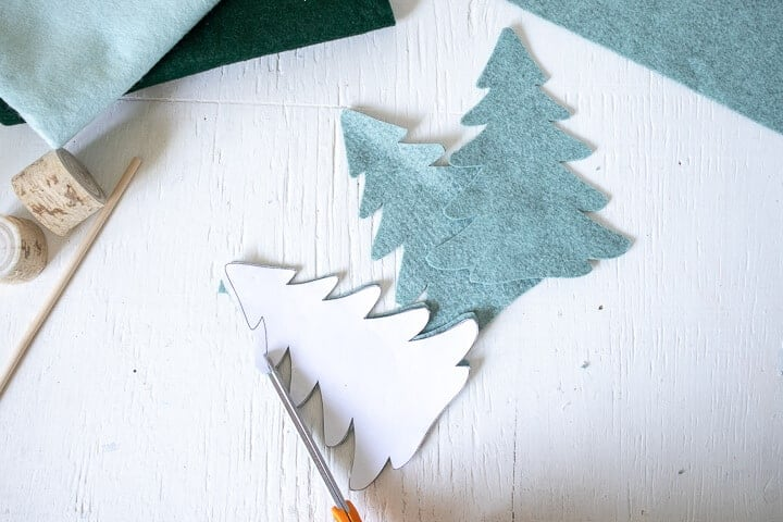 Christmas tree pattern template on top of cut felt Christmas trees