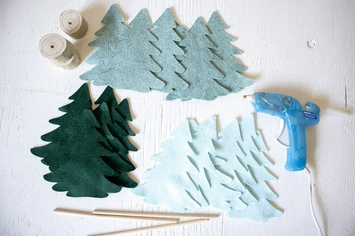 felt Christmas tree shapes on a table with a glue gun