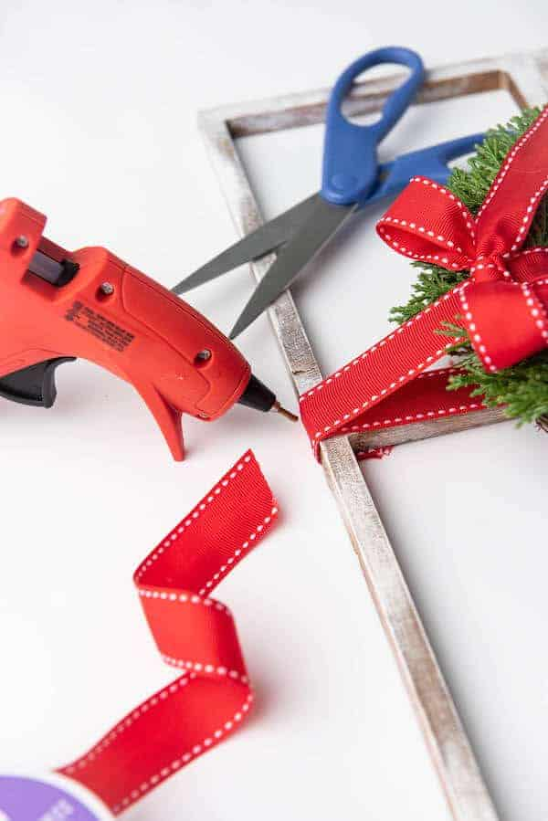 a hot glue gun being used to attach a wreath to a DIY fake window frame