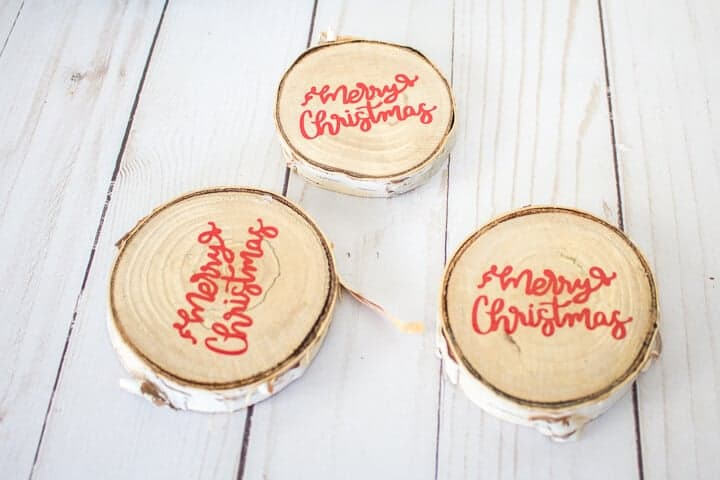 wood slice ornaments that say Merry Christmas
