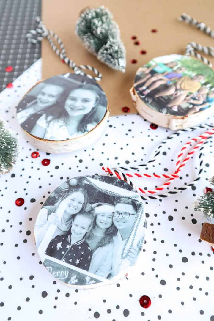 DIY wood slice photo ornaments laying on a Christmas background
