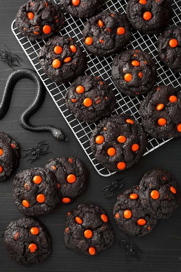 black colored cookies with orange candies on top