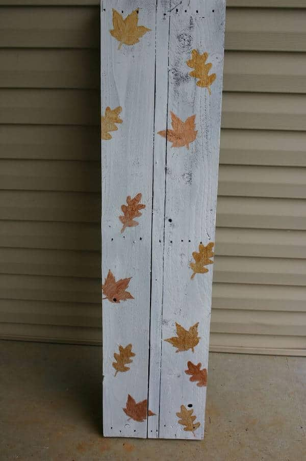 base of front porch fall sign painted white with metallic leaves