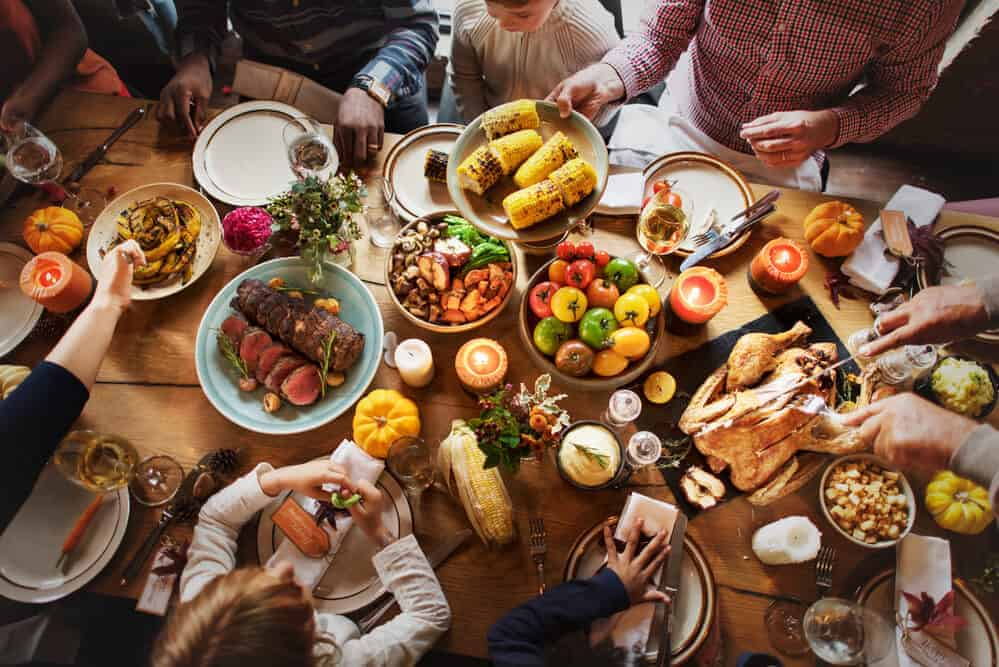 guests seated at thanksgiving dinner table