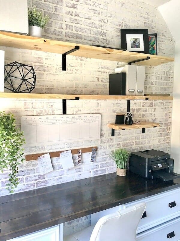 home office with open shelves and a faux brick accent wall
