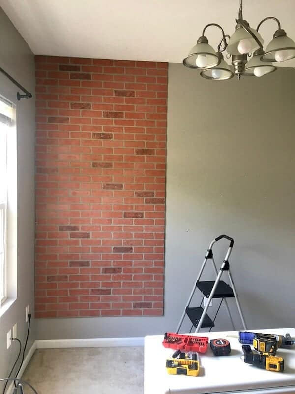 one faux brick wall panel on a gray wall