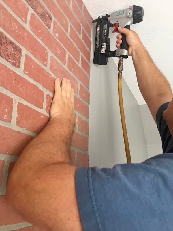 man using a nail gun on a faux brick wall panel