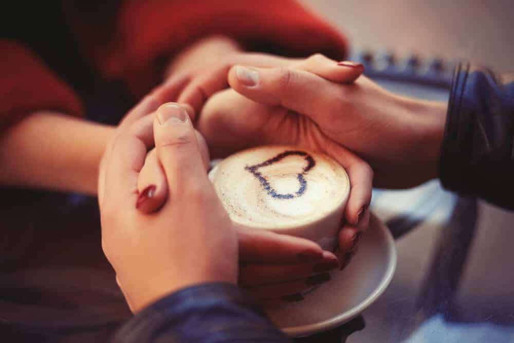 two peoples hands wrapped around a coffee cup
