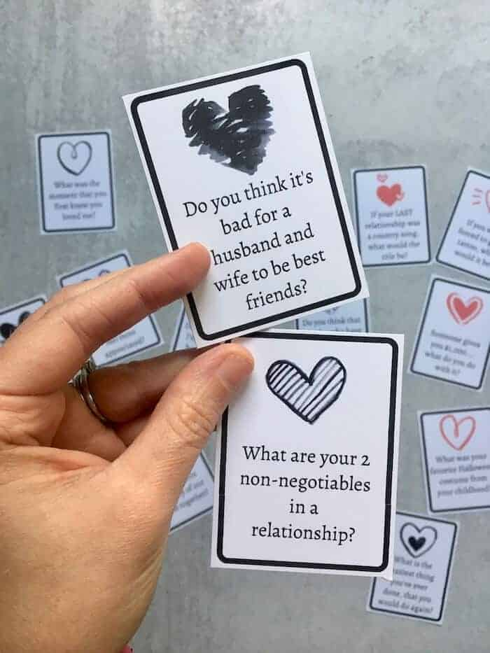 woman's hand holding 2 conversation cards