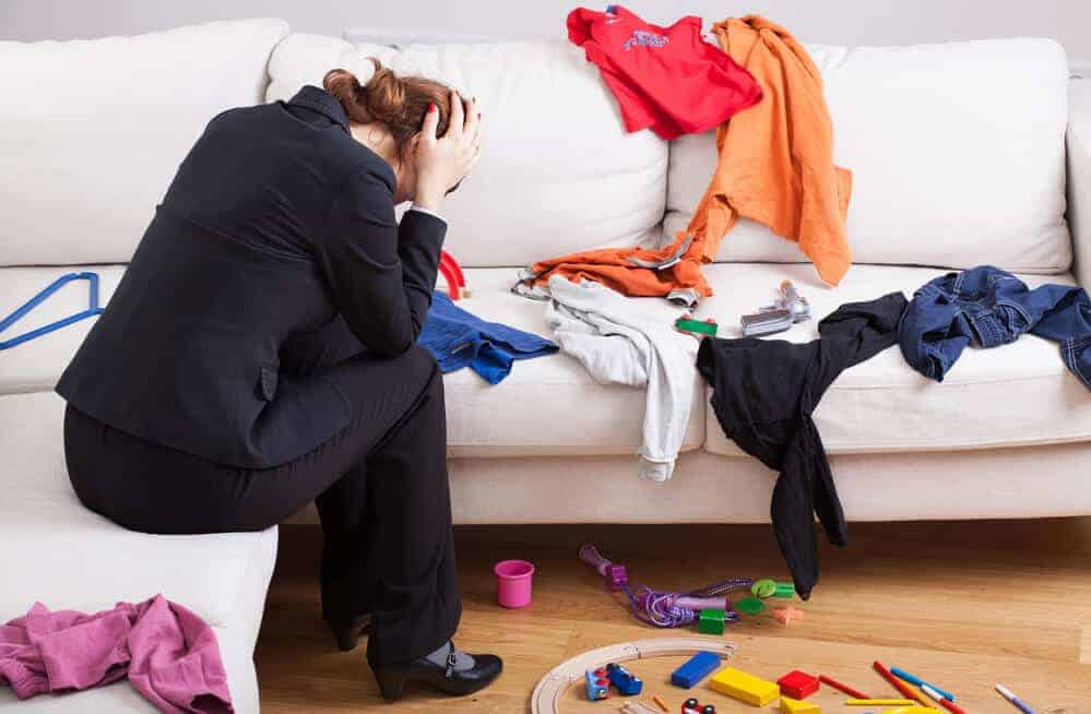 woman sitting on couch overwhelmed by clutter