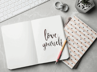 self care planner that says love yourself on a desk