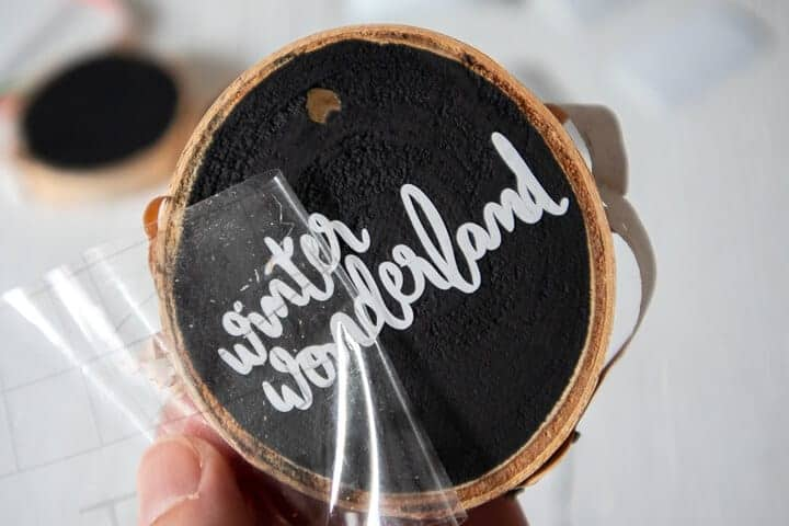 making DIY wood slice ornaments with vinyl lettering