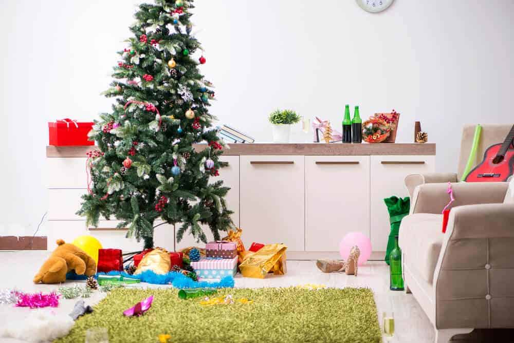 messy living room with Christmas tree and gifts
