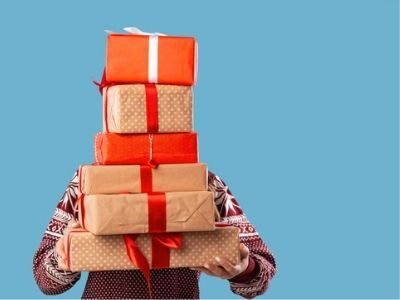 person holding a stack of Christmas gifts