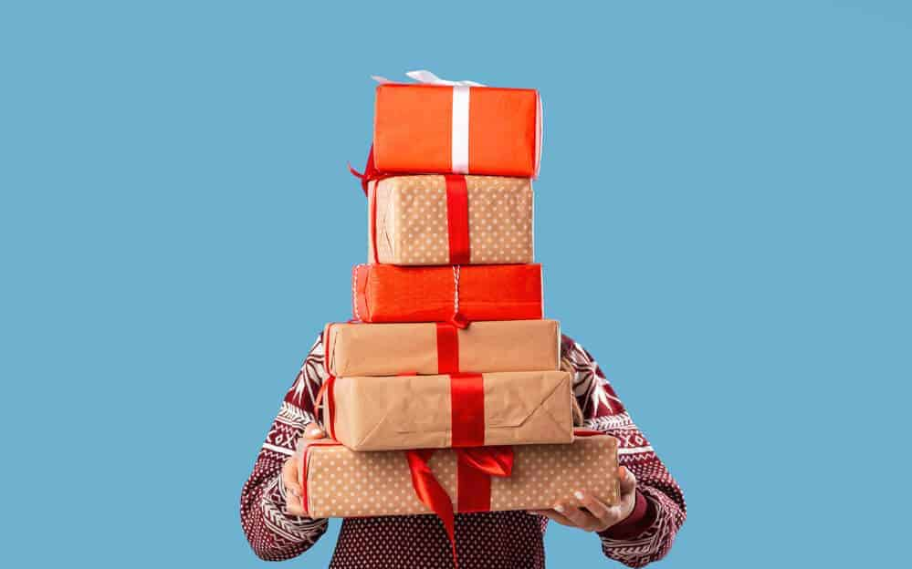 person holding a stack of Christmas presents