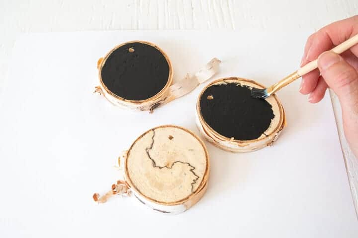 woman's hand painting wood slices black