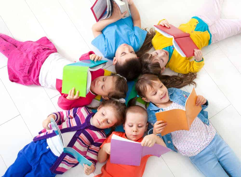 kids laying on the ground reading books