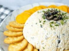 olive cheeseball on a plate with crackers