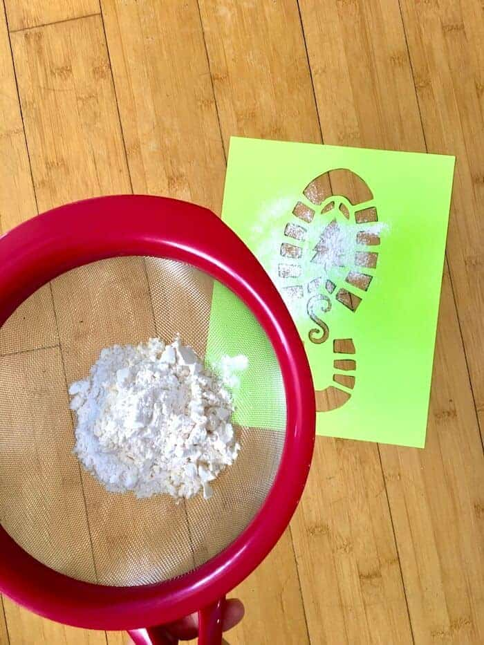 sifting flour on top of a boot print stencil