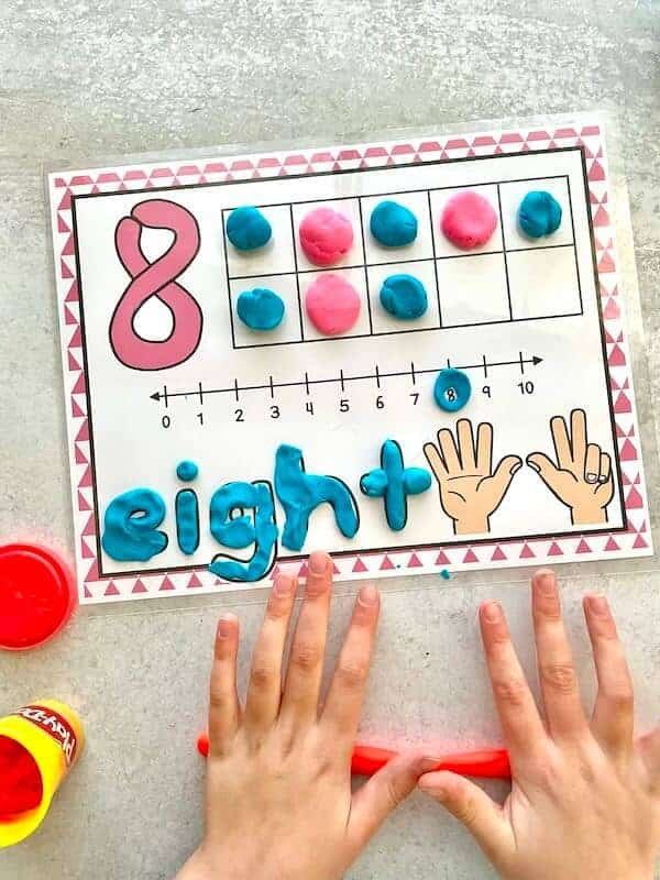 child playing with number playdough mat