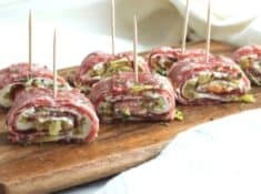 salami and cream cheese roll ups on a cutting board