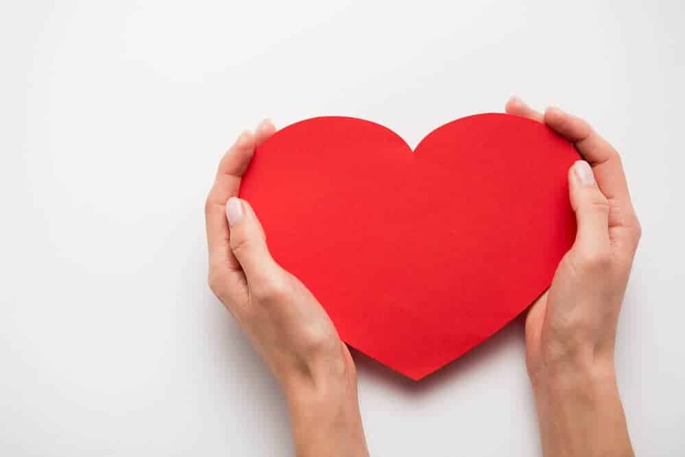 woman's hands holding a paper heart