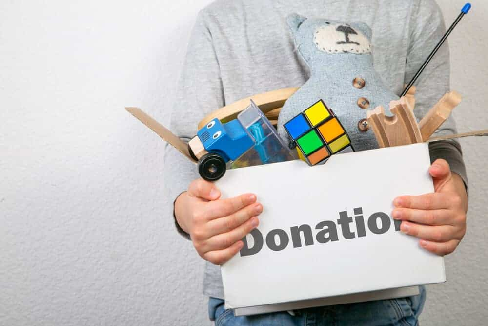 boy holding a box of toys labeled donations