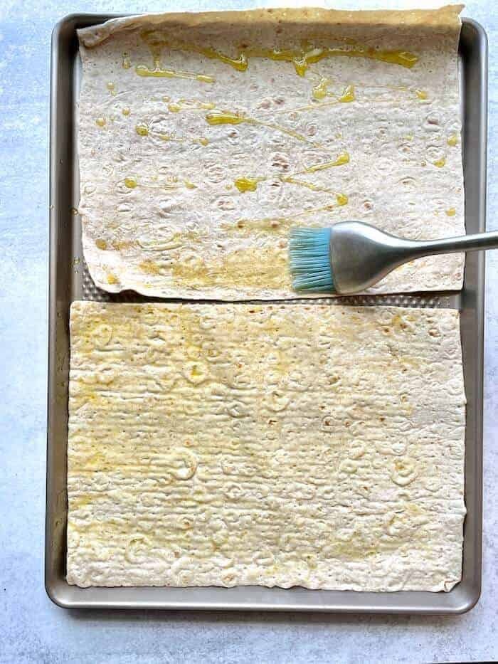 brushing olive oil on a flatbread