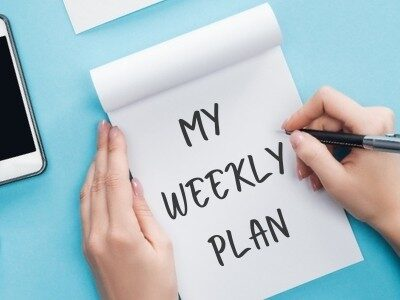 woman writing my weekly plan in a notebook