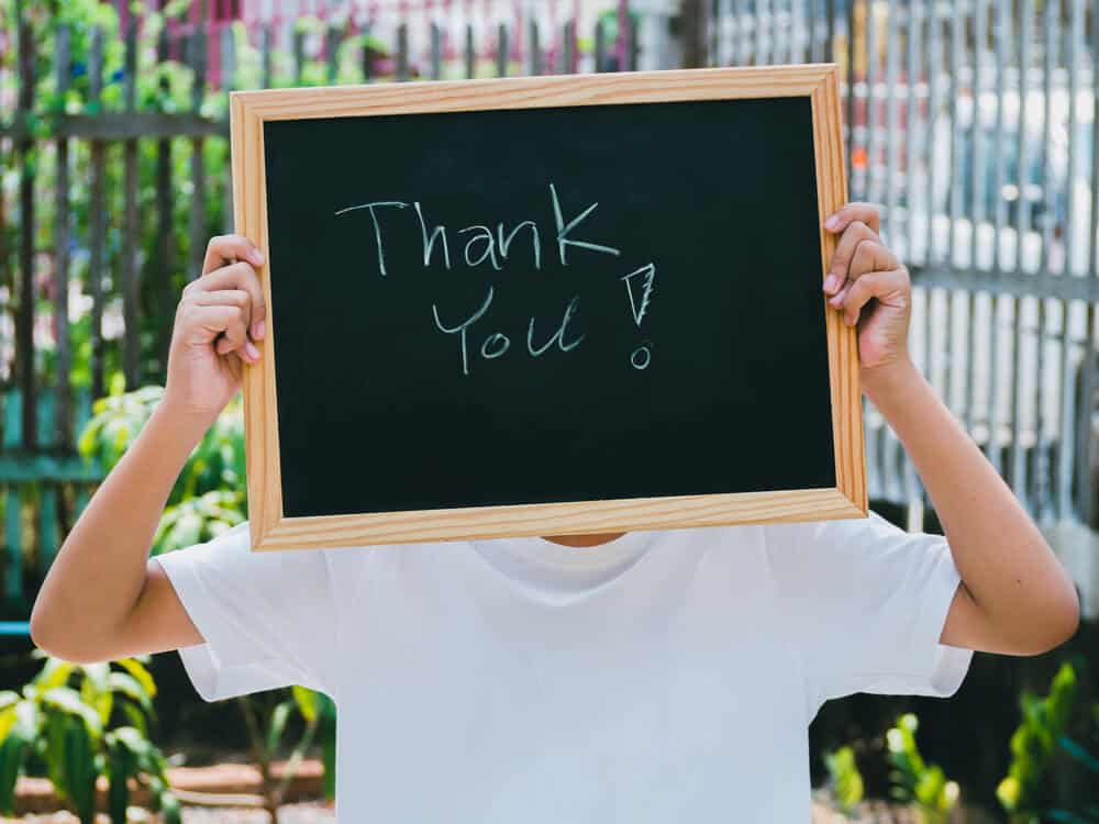boy holding a chalkboard sign that says thank you