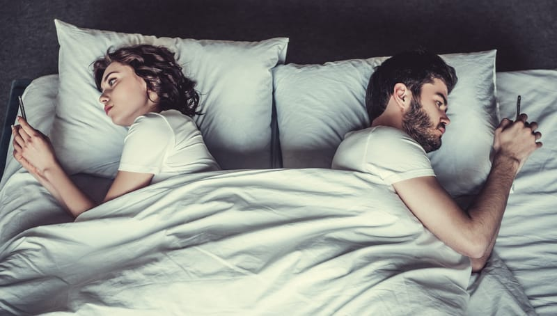 married couple laying in bed using cell phones