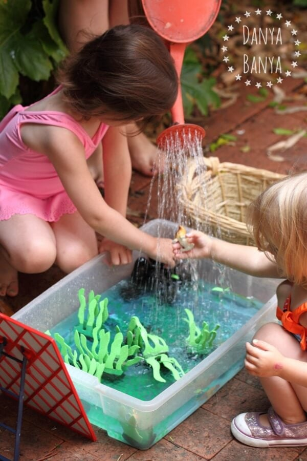 toddlers playing with a water sensory bin outdoors