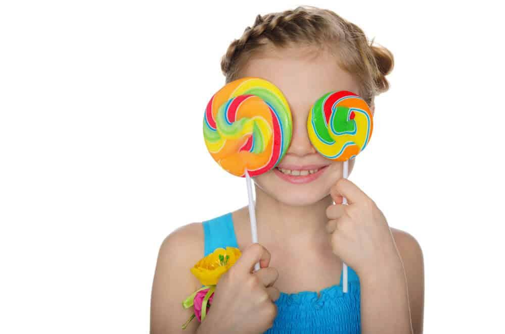 little girl with 2 lollipops
