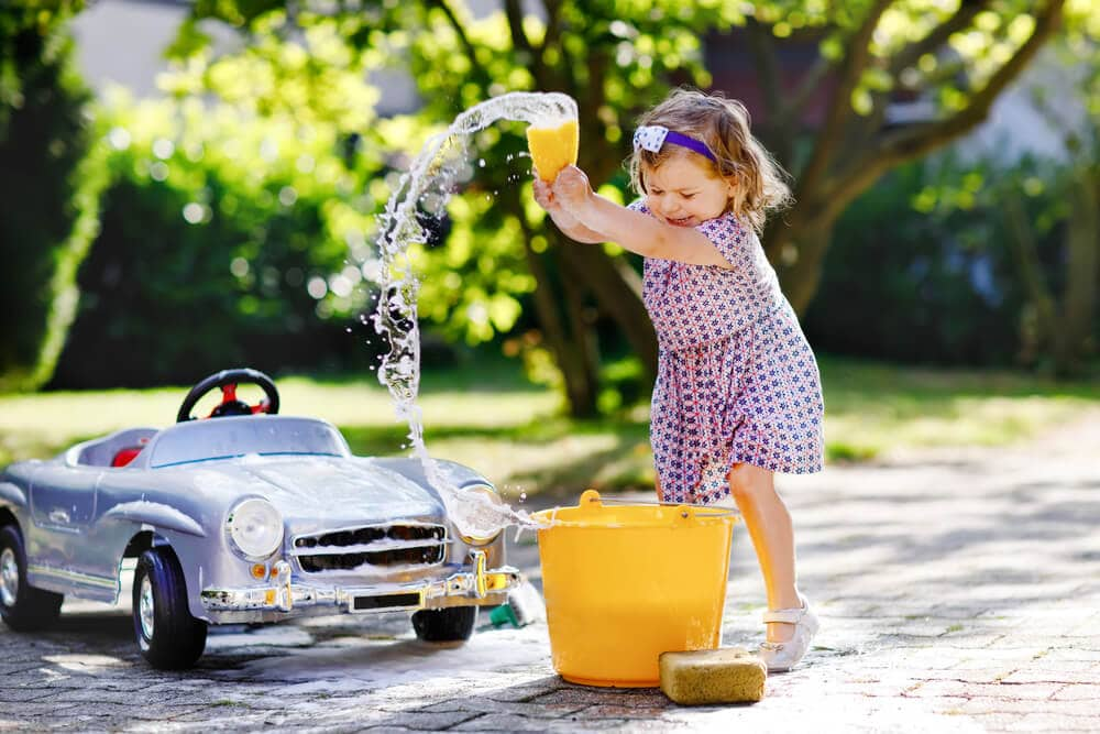 little girl washing her toy car