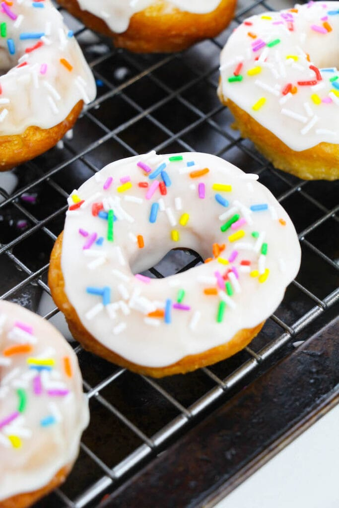 vanilla glazed biscuit donuts on a cooling rack