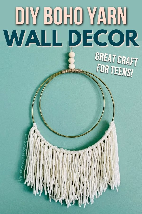 DIY boho yarn wall decor hanging on a teal wall