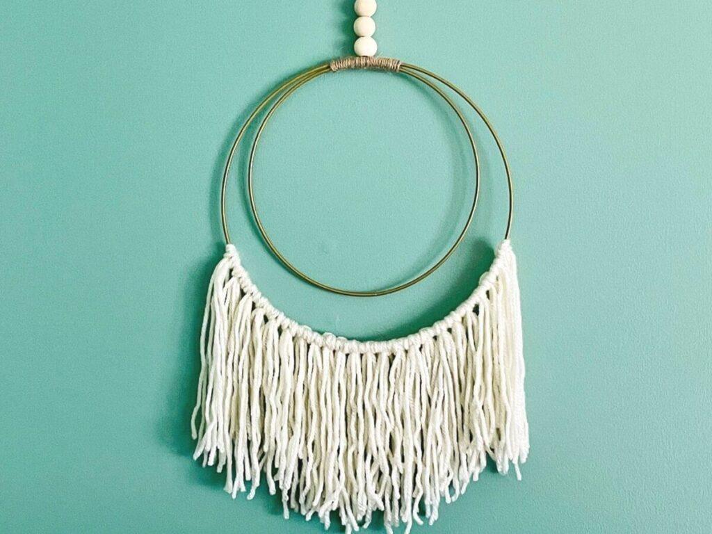 DIY boho wall hanging made with yarn and gold hoops