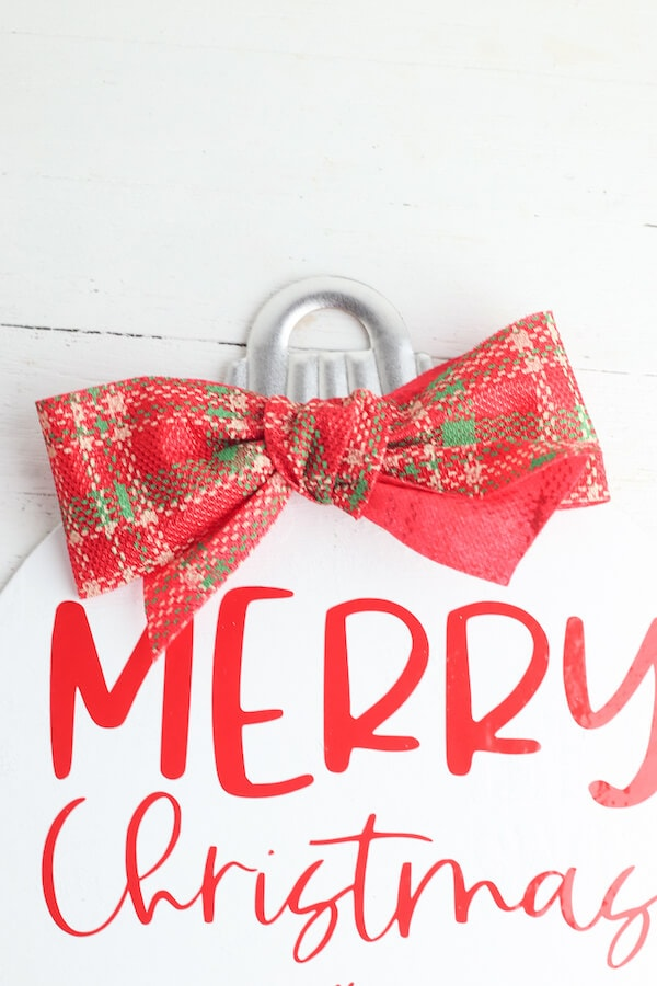 red plaid bow tied onto wood Christmas sign